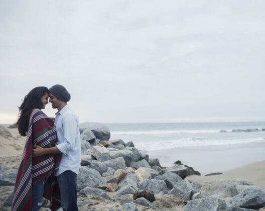 Un jeune couple face à face au bord de la mer